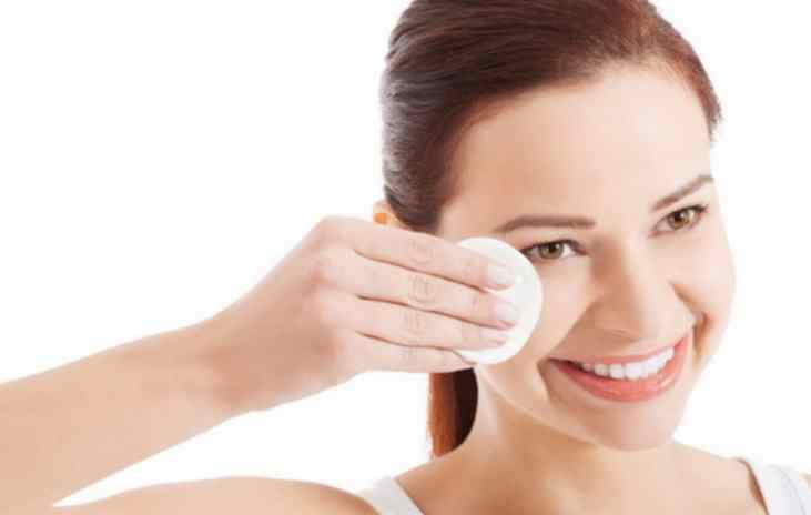 Young beautiful cleaning face with cotton pads.